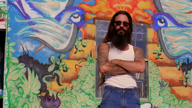vídeos de stock e filmes b-roll de low angle dolly shot portrait man with long hair, beard, sunglasses, + tattoos stands arms crossed/ tattoo parlor background - cabelo comprido