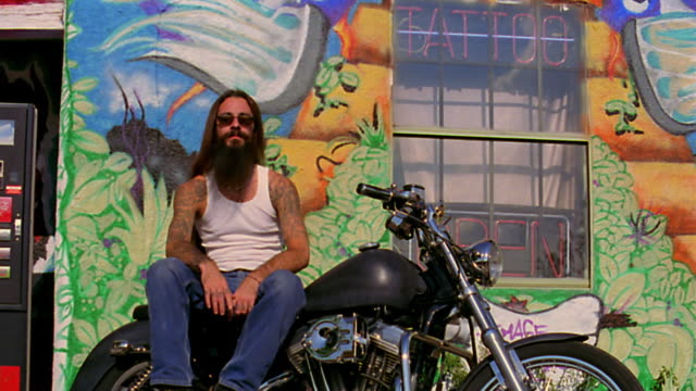 vidéos et rushes de low angle dolly shot portrait man with long hair, sunglasses + tattoos sitting on motorcycle / tattoo parlor in background - stationary