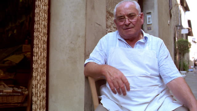 low angle dolly shot portrait senior italian man sitting in chair in front of store talking + moving hands / italy - gesturing stock videos & royalty-free footage