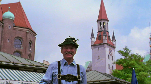 low angle dolly shot PORTRAIT toward man smiling + wearing German costume with Altes Rathaus in background / Munich, Germany