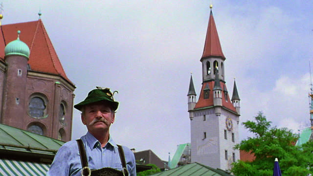 low angle dolly shot portrait toward man wearing german hat + lederhosen with altes rathaus in background / munich, germany - バイエルン州点の映像素材/bロール