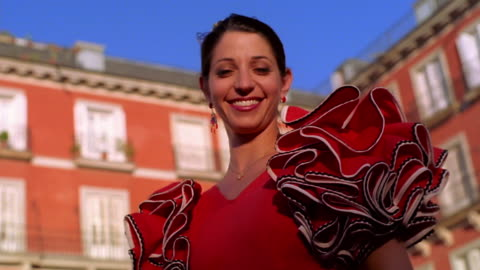 low angle dolly shot portrait woman wearing red flamenco dress + smiling / red building in background / plaza mayor, madrid - spanish culture stock videos & royalty-free footage