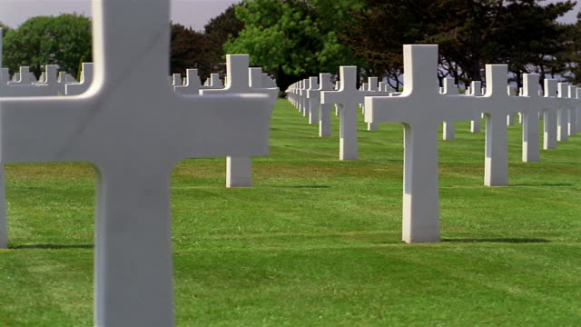 low angle dolly shot rows of marble crosses on green grass at the american cemetery / normandy - normandie stock-videos und b-roll-filmmaterial