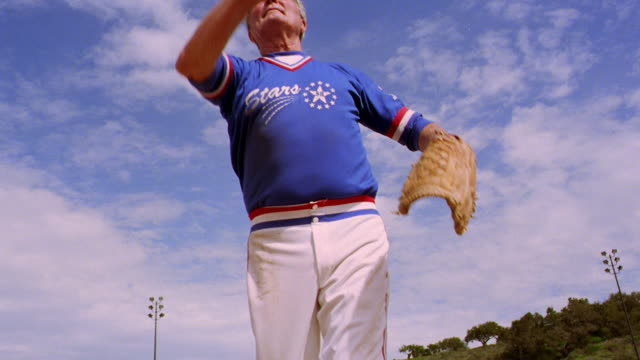 low angle dolly shot senior man in uniform pitching + catching softball in field