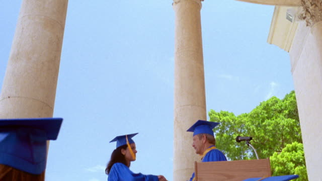 low angle dolly shot tilt down Hispanic graduates receive diplomas from man standing at podium on stage outdoors / Florida