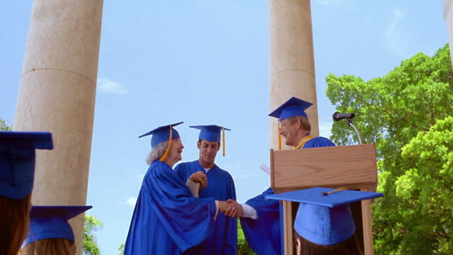 low angle dolly shot tilt down senior woman wearing cap + gown receiving diploma from man on stage outdoors / Florida