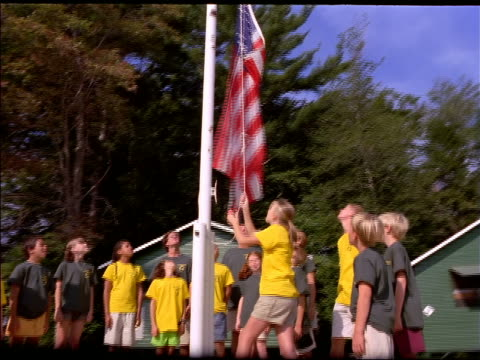 low angle dolly shot tilt up around group of children standing by flagpole as girl raises american flag at summer camp - summer camp stock videos & royalty-free footage