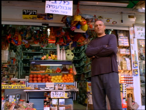 low angle dolly shot toward Israeli man standing with arms crossed in front of open air grocery store / Tel Aviv