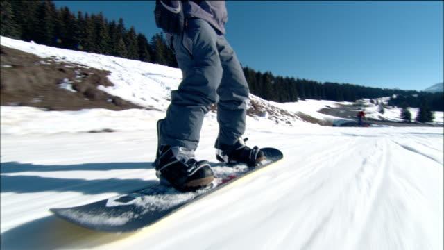 vídeos de stock, filmes e b-roll de low angle dolly shot tracking shot man snowboarding downhill with ski lift overhead - mitten
