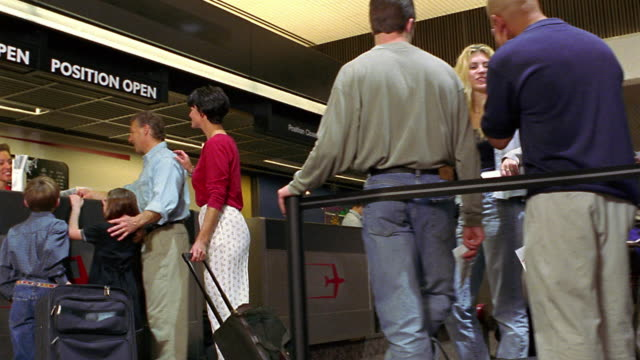 low angle MS dolly shot travelers in line waiting to check in at airport with family at ticket counter / Phoenix, AZ