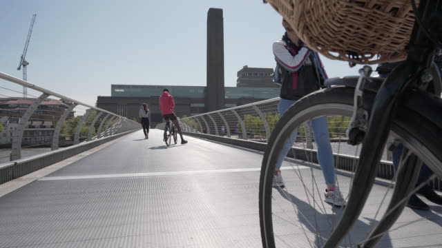 a low angle dolly shot with bicycle wheel over the millennium footbridge towards the tate modern, london - city stock videos & royalty-free footage