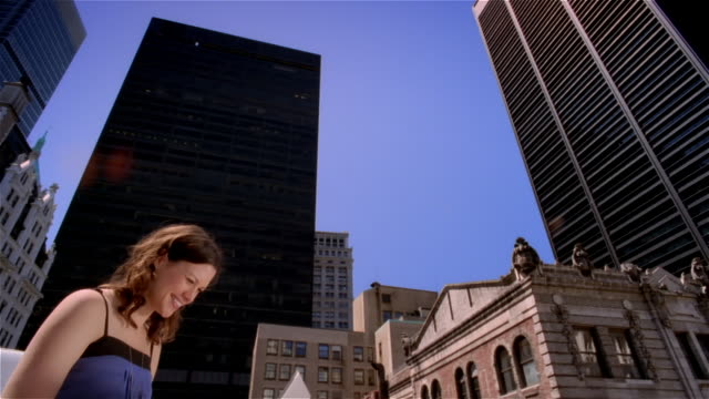 Low angle dolly shot woman sitting on rooftop using laptop computer / New York City
