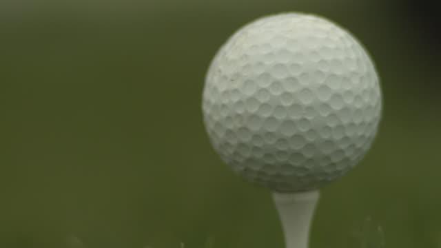vídeos y material grabado en eventos de stock de low angle driver hitting golf ball, close up - swing de golf