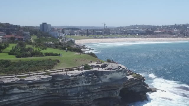 low angle drone seeing waves crashing into MacKenzies Point rocks rising up over headland to see people on coastal walk and higher towards Bondi...