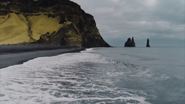 vidéos et rushes de low angle drone shot flying over ocean waves, reynisfjara, vik, iceland - low angle view
