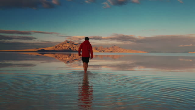vídeos de stock e filmes b-roll de low angle drone shot following an adult walking towards a mountain at sunset on the flooded bonneville salt flats, utah, united states of america - seguir atividade móvel