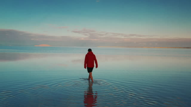 low angle drone shot showing a young adult walking on the flooded bonneville salt flats, utah, united states of america - salt flat stock videos & royalty-free footage
