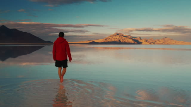 vídeos de stock e filmes b-roll de low angle drone shot showing ripples coming from a person walking on the flooded bonneville salt flats and a mountainous backdrop at sunset, utah, united states of america - geografia física