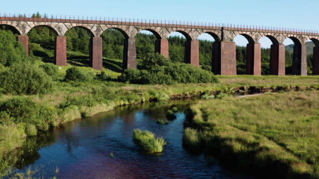 low angle drone view of a small river and disused railway viaduct in rural south west scotland - galloway scotland stock videos & royalty-free footage