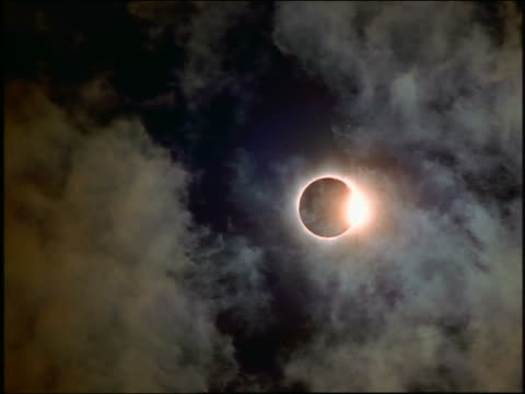 low angle eclipse past totality with clouds in foreground / Austria 1999
