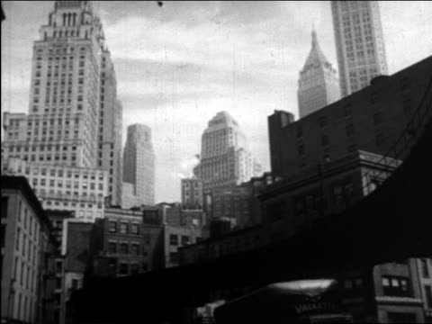 b/w 1945 low angle pan elevated train moving around corner / nyc skyline in background / educational - 1945 stock videos and b-roll footage