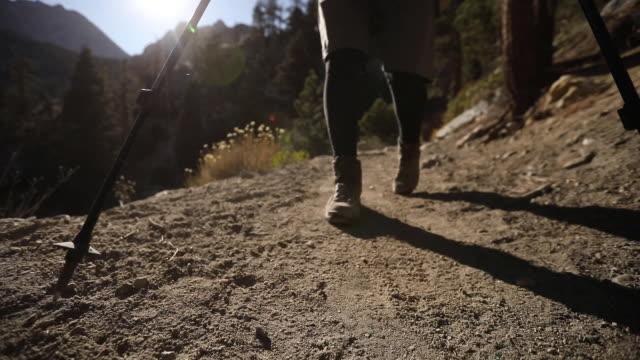 low angle establishing shot following a man hiking a dusty trail on mount whitney in california - californian sierra nevada stock videos & royalty-free footage