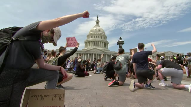 vidéos et rushes de low angle establishing shot of protesters kneeling outside the u.s. capitol building during a rally in washington d.c. following the death of george... - poing levé