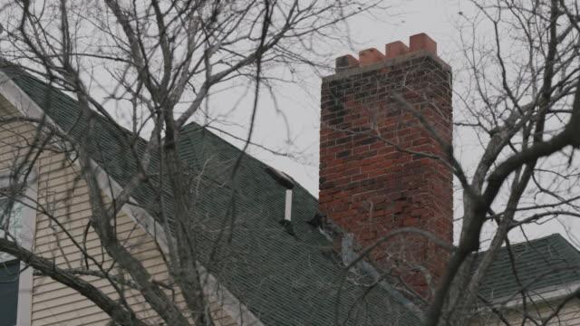 vídeos y material grabado en eventos de stock de low angle exterior shot of a rooftop with brick chimney and empty tree branches in the foreground. - casa de ladrillo