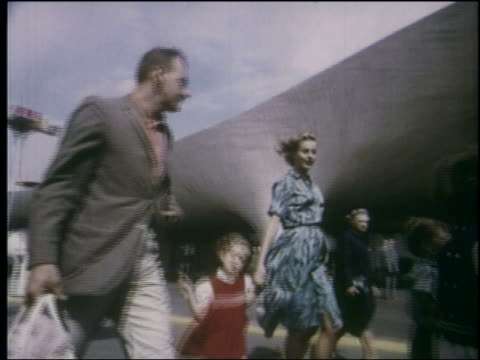 1964 low angle PAN family walking past odd curved building at NY World's Fair