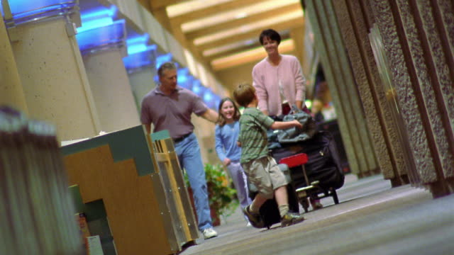 CANTED low angle family walking through Phoenix Airport with mother pushing luggage cart / Arizona