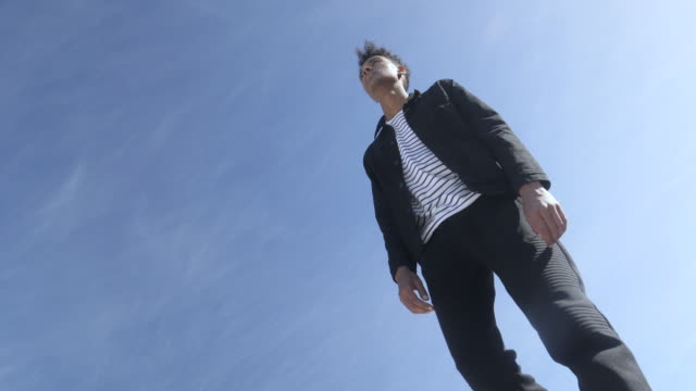 low angle, fashionable mixed race man jumps - low angle view stock videos & royalty-free footage