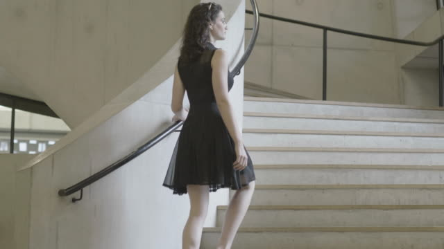 low angle, fashionable woman in black dress climbs stairs in heels - black dress stock videos & royalty-free footage