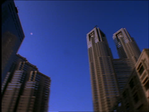 low angle fast PAN of skyscrapers in Tokyo / Shinjuku / blue sky in background