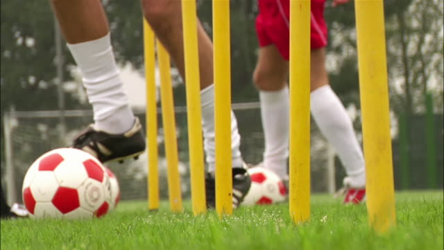 low angle feet of three soccer players dribbling soccer balls around poles - pole stock videos & royalty-free footage