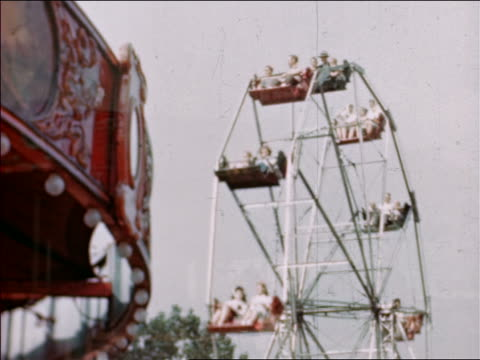 1946 low angle ferris wheel with part of carousel in foreground at state fair / dissolve into carousel / industrial / - 回転遊具点の映像素材/bロール