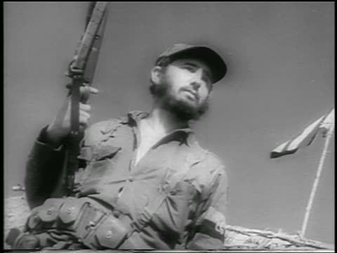CANTED low angle Fidel Castro in military uniform holding gun outdoors / Cuba / newsreel