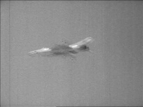 b/w 1967 low angle pan fighter jet moving across sky in six day war / newsreel - sechstagekrieg stock-videos und b-roll-filmmaterial