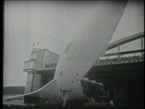 B/W 1969 low angle first Concorde plane being towed out of airplane hangar in France