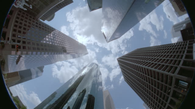 low angle fisheye point of view houston skyscrapers / blue skies + clouds in background - fish eye lens stock videos & royalty-free footage