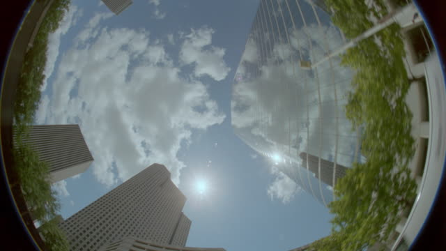 low angle FISHEYE point of view Houston skyscrapers / blue skies + clouds in background