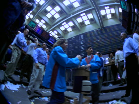 BLUE low angle FISHEYE slow motion PAN traders shaking arms + shouting under display board / Commodity Exchange