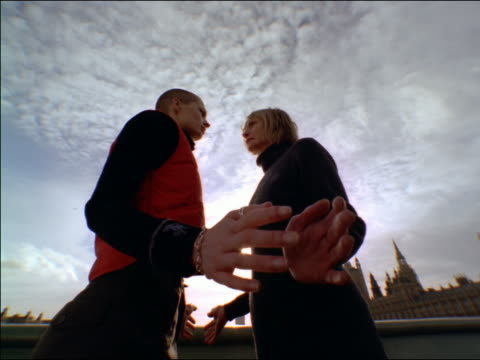 low angle FISHEYE young woman with shaved head facing + touching hand of middle-aged blonde woman