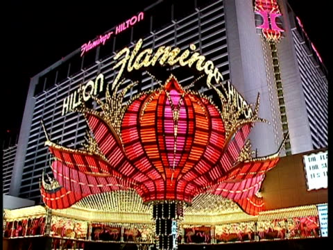 wa low angle, flamingo hilton with giant flower sign in neon lights, camera zooms in to extreme close up of lights, las vegas - flamingo hilton stock videos & royalty-free footage