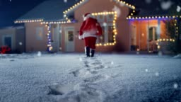 Low Angle Footage of Santa Claus with Red Bag, Walks into Front Yard of the Idyllic House Decorated with Lights and Garlands. Santa Bringing Gifts and Presents at Night. Magical New Year's Eve with Falling Snow.