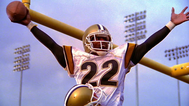 low angle MS football player holding up second player with ball in raised arms in celebration in end zone