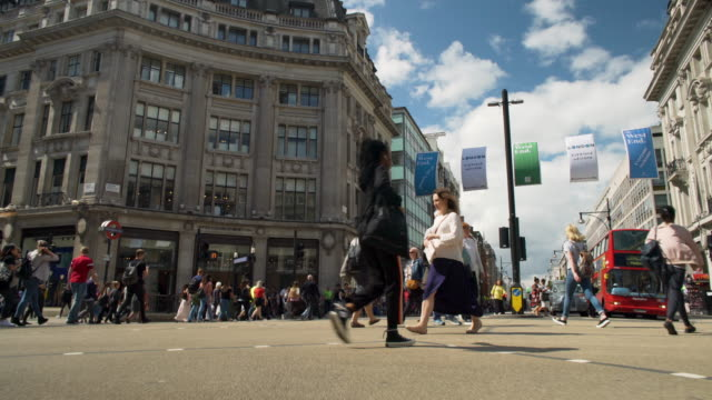 low angle forward tracking shot across oxford circus. - oxford street stock-videos und b-roll-filmmaterial