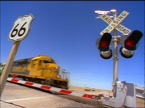 vidéos et rushes de low angle pan freight train passing train crossing on route 66 / southwestern us - plaque de rue