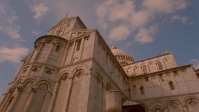 low angle PAN from church to leaning Tower of Pisa / Italy