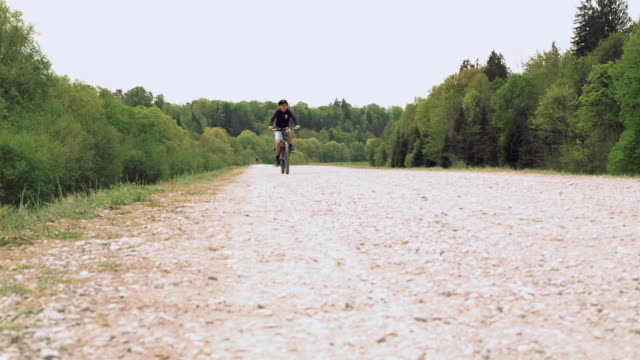 low angle front view boy biking on a trail - 8 9 years stock videos & royalty-free footage