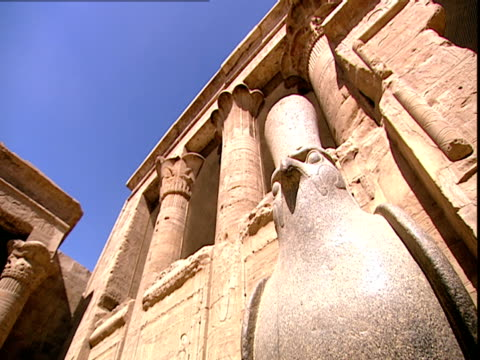 low angle front view of the granite statue of horus as a falcon with giant carved granite columns in the background at the entrance of the great... - in front of点の映像素材/bロール